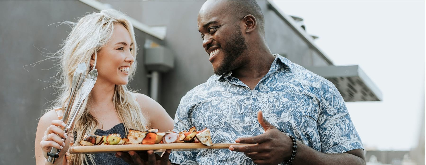 man and woman smile at each other while holding a cutting board of kabobs and grilling tongs